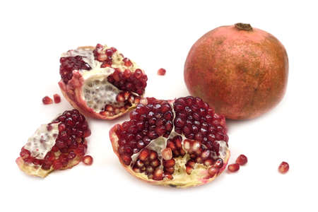 Whole and half pomegranates with ripe seeds isolated on white background Foto de archivo