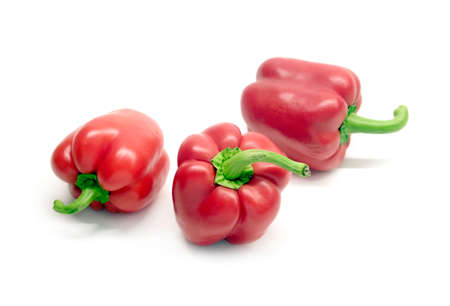 Still life with three whole red ripe bell peppers isolated on white background close up Stock Photo