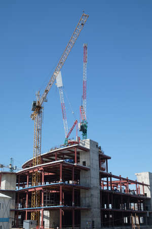 Tower cranes on industrial building process, on blue cloudless sky Stock Photo