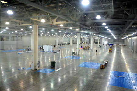 Large empty warehouse interior in an industrial building with high vertical columns 스톡 콘텐츠
