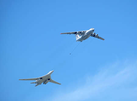 MOSCOW, RUSSIA - May 9, 2018: Russian military transport plane Il-78 refueling tankers imitates refueling the Supersonic bomber-missile carrier TU-160 Whire Swan in flight against the blue sky