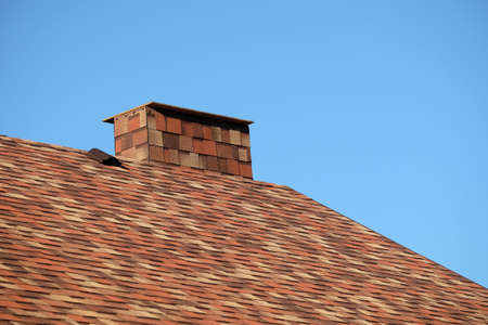Part of a brown roof of a house covered with motley soft shingles with short big smokestack close up under cloudless blue sky on sunny day