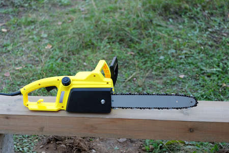 Electric saw on brown wooden balk ready for work outdoors