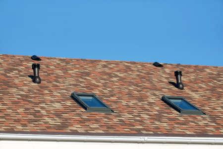 Roof windows, ventilation tubes on motley roof