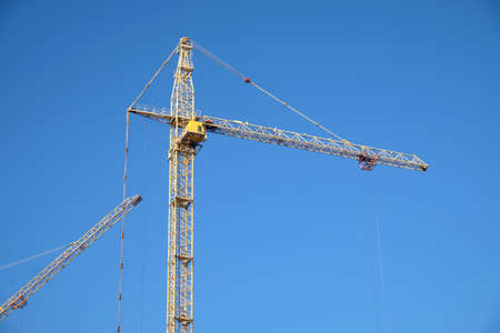 Big yellow construction tower crane over clear blue sky