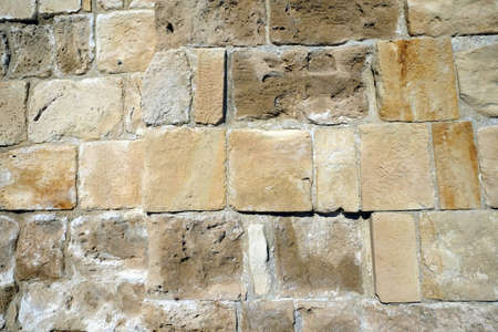 Ancien stone wall as background front view closeup