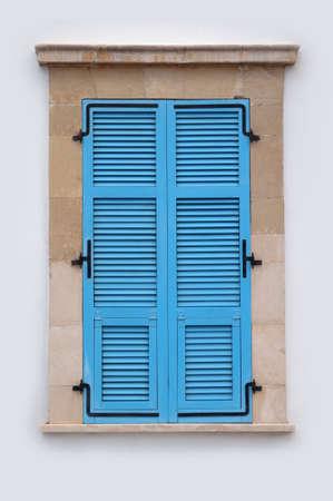 Neat blue window with closed shutters on beige wall Banco de Imagens