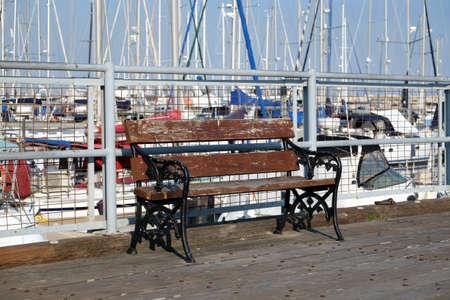 Bench on pier where sea yachts dense parking Banco de Imagens