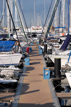 Pier with many parking yachts in calm marina water