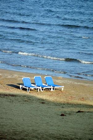 Empty beach with three sun loungers on sand near sea Banco de Imagens