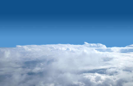 View from airplane above white clouds in the sky Banco de Imagens