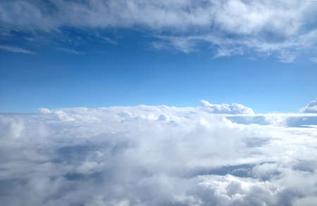 View from airplane through white clouds in the sky