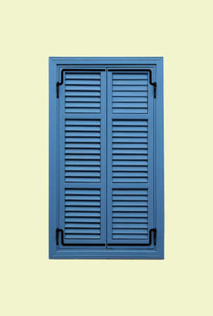 Blue vertical window with closed shutters on beige wall