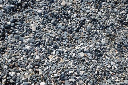 Smooth pebble stones on the beach top view Banco de Imagens