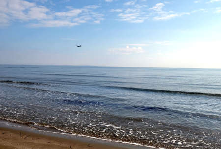 Passenger airplane flying in the sky above calm sea