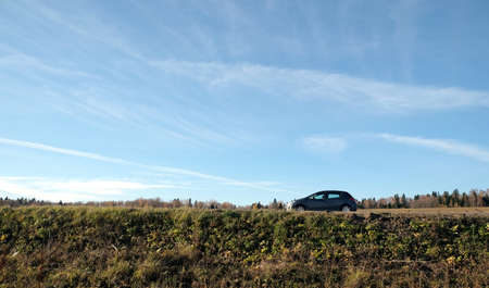 Passenger car in panorama autumn landscape side view