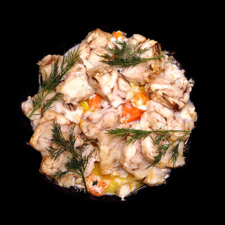 Fried white fish fillet with carrot and dill isolated on black
