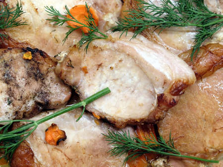 Roasted pork meat steaks with carrot top view closeup