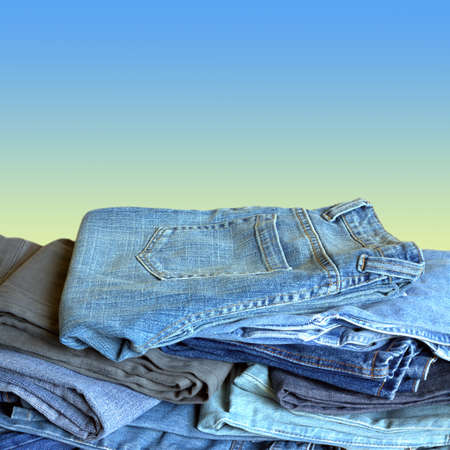 Fashion jeans lie in stacks over gradient background Banco de Imagens