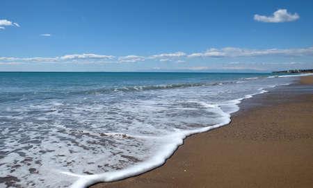 Sandy sea beach with high mountains on skyline