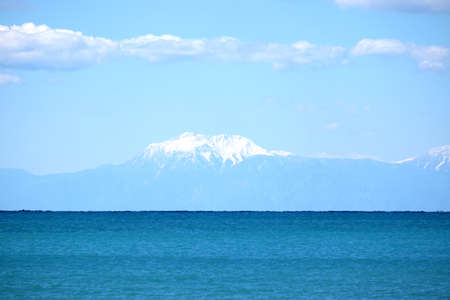 Mountains with snow caps far after the sea