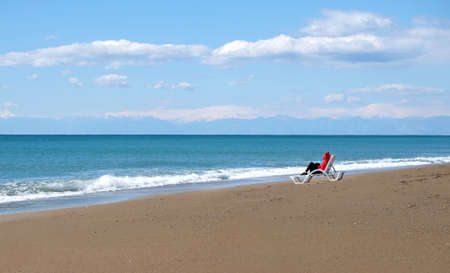 Lonely female tourist sits on long empty sandy beach