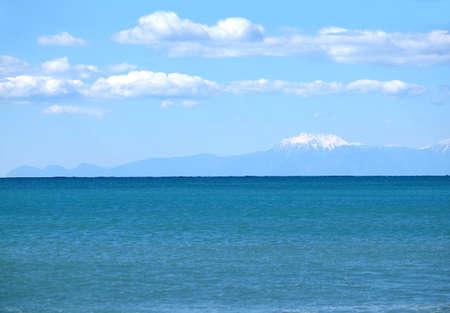 Mountains contours with snow caps far after the sea Banco de Imagens