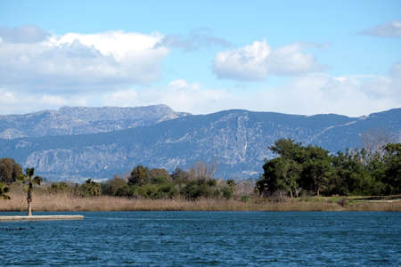 Lake, pine forest and high mountain slopes in spring