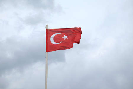 Turkish red flag waving on gloomy rainy day