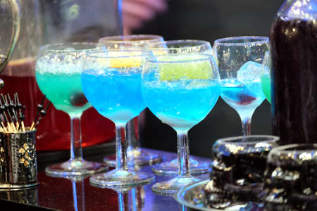 Colorful cocktails with ice on nightclub bar counter Banco de Imagens