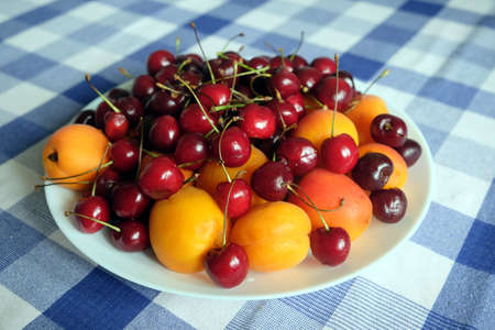 Healthy eating. Plate with ripe fruits on checkered tablecloth close up Banco de Imagens