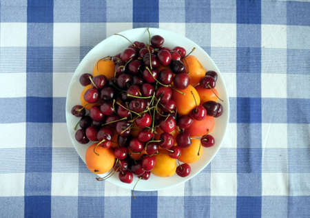 Healthy eating. Plate with ripe fruits on checkered tablecloth top view close up