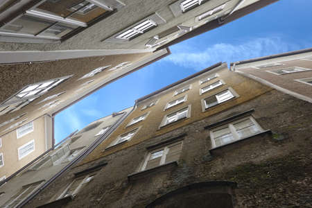 Dense standing buildings on narrow street bottom up view Banco de Imagens