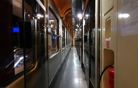 Perspective view of empty night corridor inside railroad car