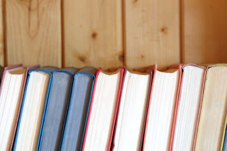 Stack of books standing on bookshelf against wooden wall front view close up