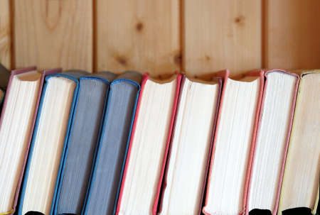 Line of books standing on bookshelf against wooden wall front view Banco de Imagens