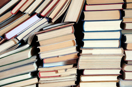 Heap of assorted retro hardcover books casually lies in stacks as background front view