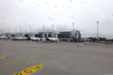 Munich international airport unfocused view from plane window with water drops on the glass in rainy weather