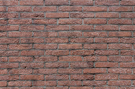 OLd wall from many small red bricks as background closeup front view horizontal