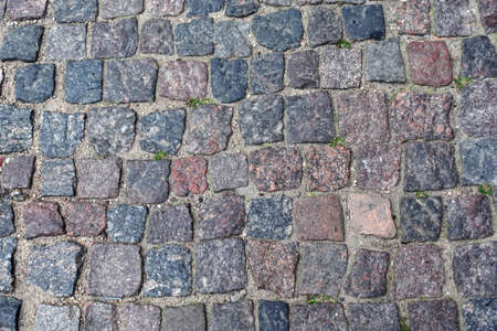 Old paving cobblestone outdoors as background top view close up