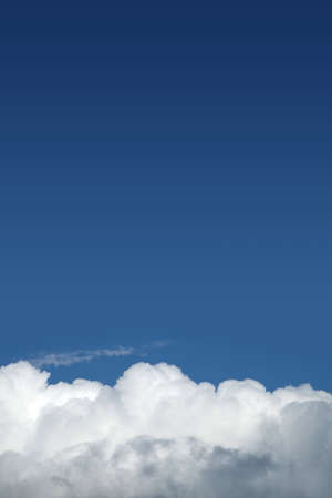 Beautiful sky landscape with white clouds on the bottom fo photo and gradient blue sky above on bright sunny day vertical view