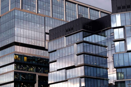 Facade with glass walls of modern office building cluster with many large panoramic windows in gray colors front view close-up