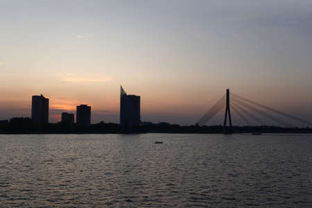 Beautiful view of cable-stayed bridge across the Daugava river in Riga forward on sunset front view Banco de Imagens