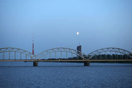 Long metal railroad arched bridge across the Daugava river in Riga against stand alone building, TV tower and bright moon forward view on sunsetsky