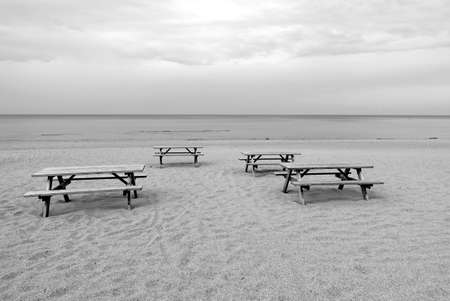 Several wooden tables and benches on empty sandy beach in Jurmala at the end of summer season black and whiet photo in retro slyle