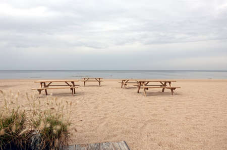 Several wooden tables and benches on empty sandy beach in Jurmala at the end of summer season photo in pastel colors