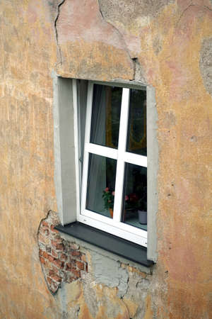 An opened new plastic window with white frame on threadbare house wall covered with plaster side view vertical closeup
