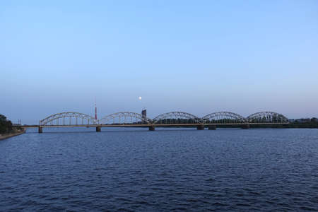 Long metal railroad arched bridge across the Daugava river in Riga against stand alone building, TV tower and bright moon forward view on sunset sky Banco de Imagens