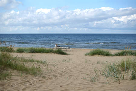 Alone woman warm covered sitting on the bench on sandy beach in Jurmala at the end of summer season and looking far to the sea waves photo in pastel colors