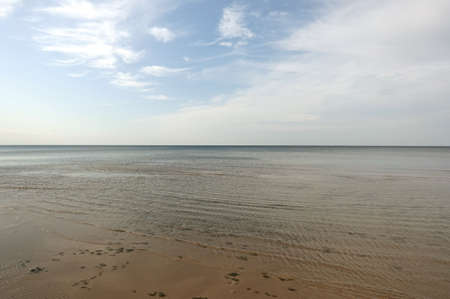 Sandy shoal of the cold Baltic Sea in the Gulf of Riga in Jurmala on low season in calm sunny day